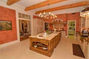 The kitchen is graced by not only a charming chandelier, but also a massive marble topped center kitchen island.