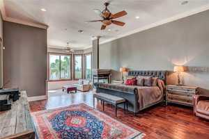 """The master bedroom has a warm, """"loft"""" vibe-- boasting a first-class view, breakfast bar, and maple brown hardwood floors. There are 6 bedrooms and 7 bathrooms total in the home. Of course, all upstairs bedrooms are en suite."""