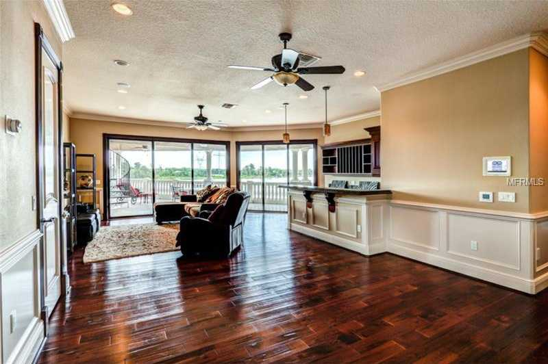 The second floor loft room features a full bar and private balcony access to enjoy breathtaking sunsets. This room is perfect for entertaining. Not shown are the home's multiple wet bars and wine cellar.