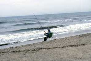 1987: An unidentified man fishing in the surf in New Smyrna Beach