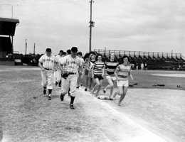 1950: Photo of some of the New York Giants doing warmup exercises with the Sanford Girls' team