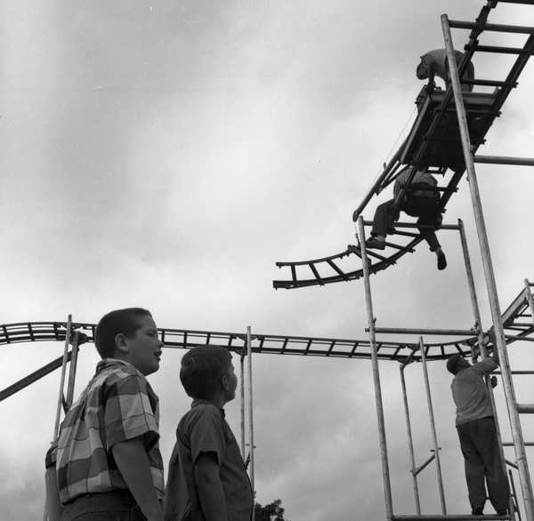"""1959: Children watch the construction of the """"Mad Mouse"""" ride at the North Florida Fair."""