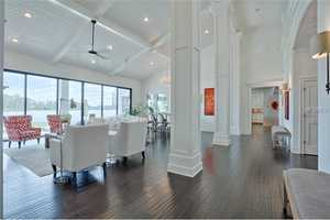 Note the contrast of dark hardwood floors to bright white walls and furniture.