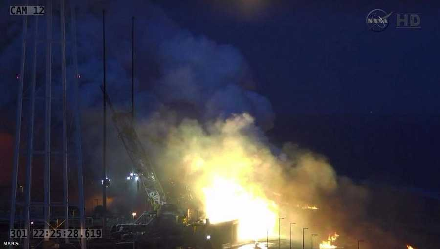 Smoke rises from launch pad after Antares rocket explosion.