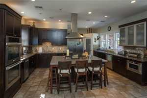 The kitchen was remodeled in 2008 with Silestone countertops, custom tiled backsplash, SS appliances including 6-burner gas range, ice maker and double-oven, two sinks and walk-in pantry.