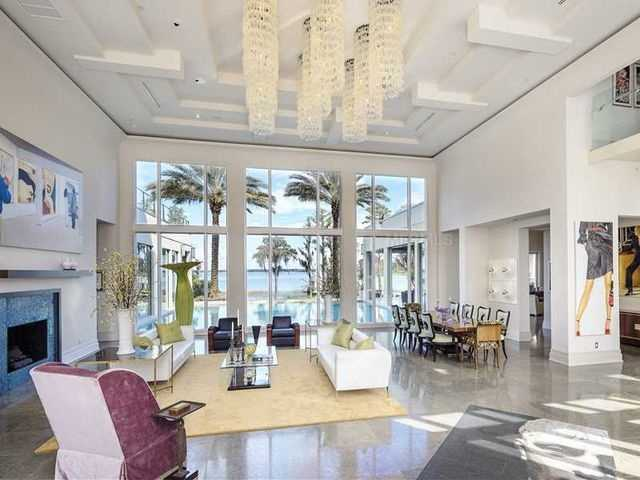 Incomparable luxury and natural light flood the open living room space. The most amazing features are the fireplace, floor-to-vaulted ceiling windows, and the nine custom chandeliers