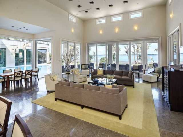 Light colors in the living room reflect the the beautiful sunlight and compliment the sparkling lake view.