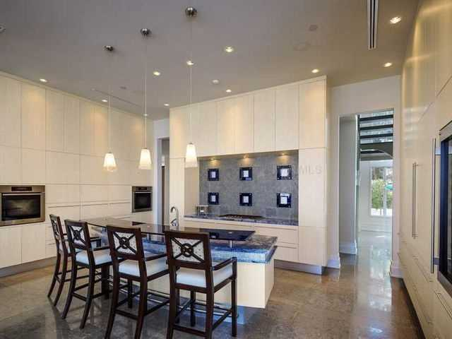 The kitchen can be summed up in two words-- modern and sleek. The cabinetry is completely minimalist and the gas stove features a gorgeous tile backsplash.