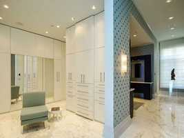 This closet is something from a fantasy. It boasts marble floors, custom cabinetry/ shelving similar to those in the kitchen, and flattering lighting.
