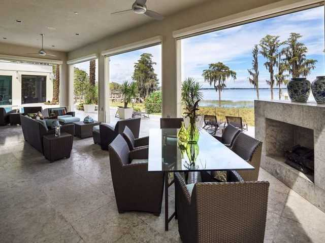 Expansive outdoor patio with fireplace is nestled between a flawless pool view and a sparkling lake view.