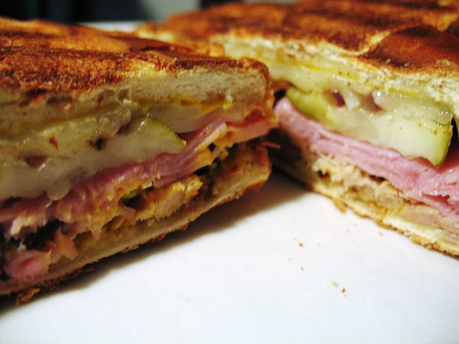 "5. Cuban Sandwich The Cuban Sandwich is made with ham, roasted park, Swiss cheese, pickles, mustard and sometimes salami on Cuban bread. It became a popular Florida delicacy in the 1960s when there was an influx of Cuban immigrants. The sandwich was designated as the ""signature sandwich of the city of Tampa"" by Tampa's city council in 2012. Best spot to get it: Los Autenticos Sandwich Cuban cafe, 7339 E. Colonial Dr.,#1, Orlando, FL 32807, get more info on Los Autenticos here."