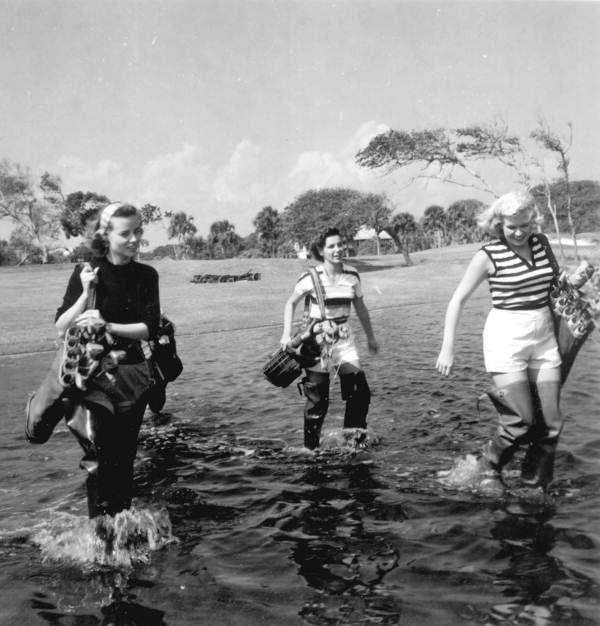 1953 - Women carry the equipment through the water in Daytona Beach