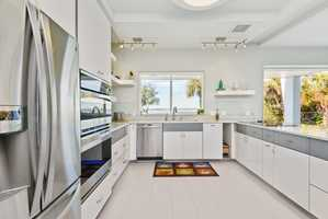 Gourmet kitchen is bright and open, featuring top-of-the-lines appliances and fresh cabinetry.