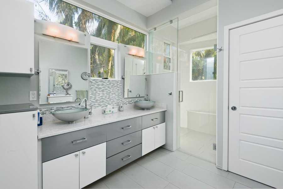 En suite bathroom boasts dual vanities, panoramic views, and a huge shower.