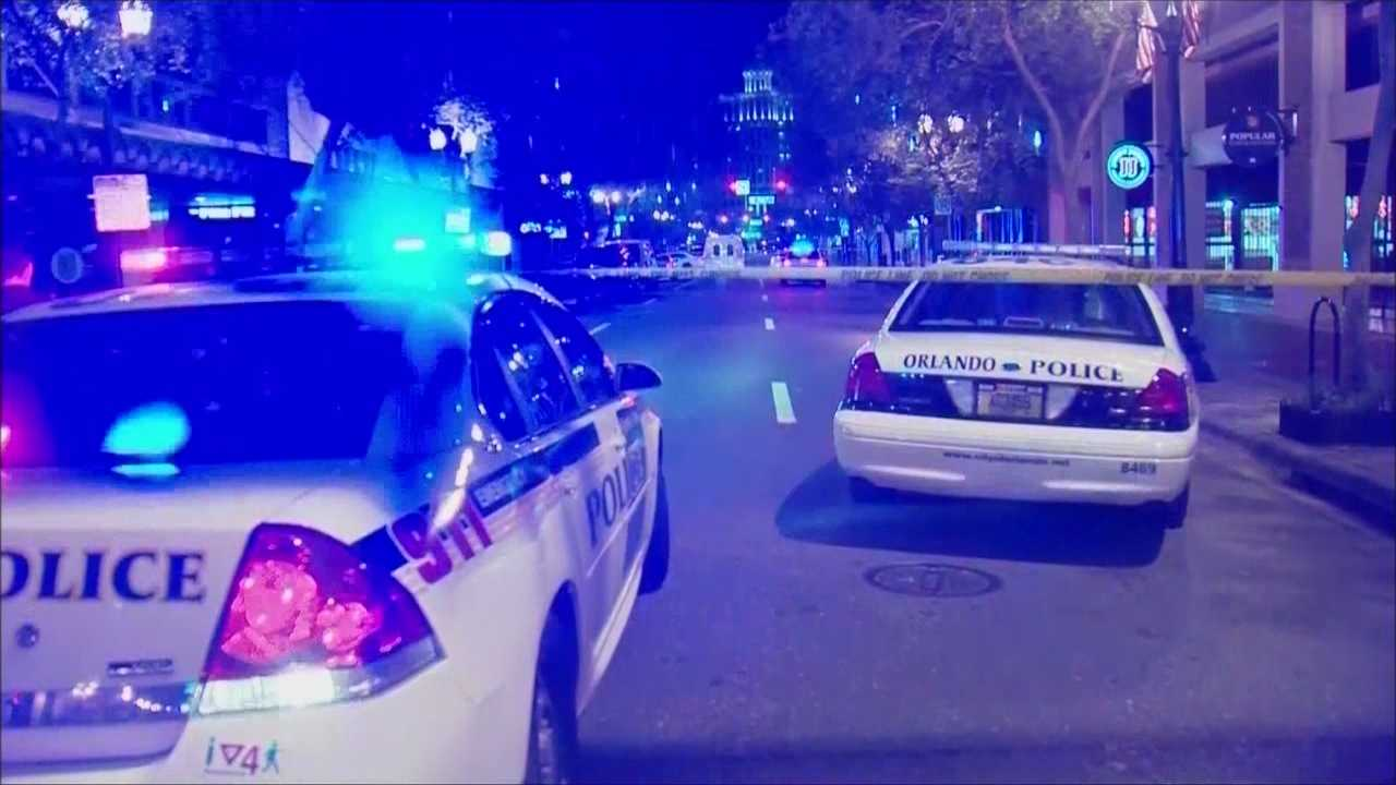 An Orlando police officer who shot and killed a woman while firing at an armed man in downtown Orlando has been cleared of any wrongdoing.
