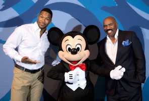 """""""LIVE! with Kelly and Michael"""" co-host Michael Strahan (left) poses March 8, 2015 with Mickey Mouse and radio and television personality Steve Harvey (right) at Epcot in Lake Buena Vista, Fla. during a break from speaking at Disney Dreamers Academy with Steve Harvey and Essence Magazine. The eighth annual event, taking place March 5-8, 2015 at Walt Disney World Resort, is a career-inspiration program for 100 distinguished high school students across the U.S. (Gregg Newton, photographer)"""