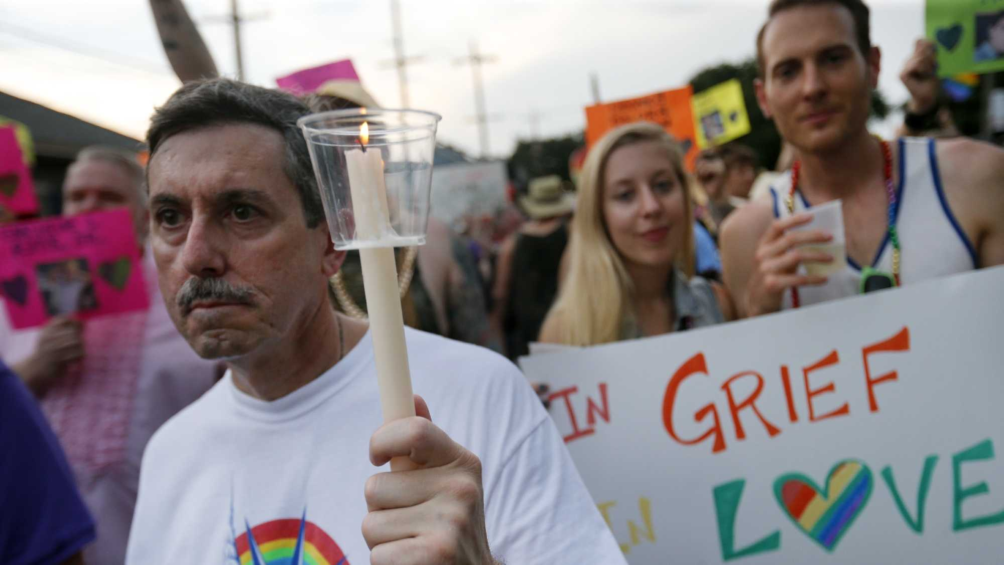 "Nick Mosca, of New Orleans, holds a candle in honor of the victims of the Orlando Pulse nightclub massacre, in the ""New Orleans Pride"" parade, a gay pride parade, in New Orleans, Saturday, June 18, 2016."