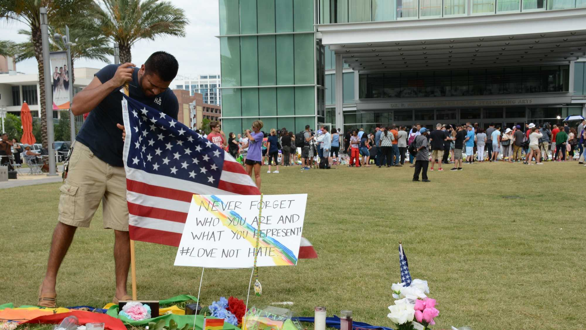 Jose Luis Nevarez secures an American flag into the ground near the memorial for those killed in the Orlando shooting.Nevarez grew up in Orlando and went to high school with one of the victims who was killed.