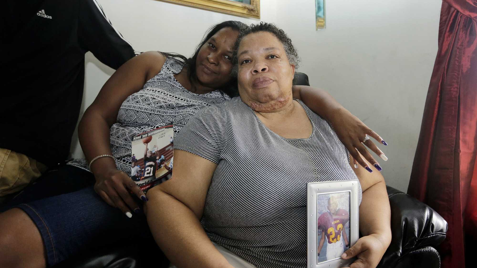 Stephanie White, right, holds a photograph of her son Stef'an Strawder during an interview in her home in Lehigh Acres, Fla., Monday, July 25, 2016. Strawder, 18, was killed in the deadly shooting outside the Club Blu nightclub in Fort Myers, Fla., Monday. Police said the gunfire, which erupted at a swimsuit-themed party for teens, was not an act of terrorism. At left is Kasey Jones. (AP Photo/Lynne Sladky)