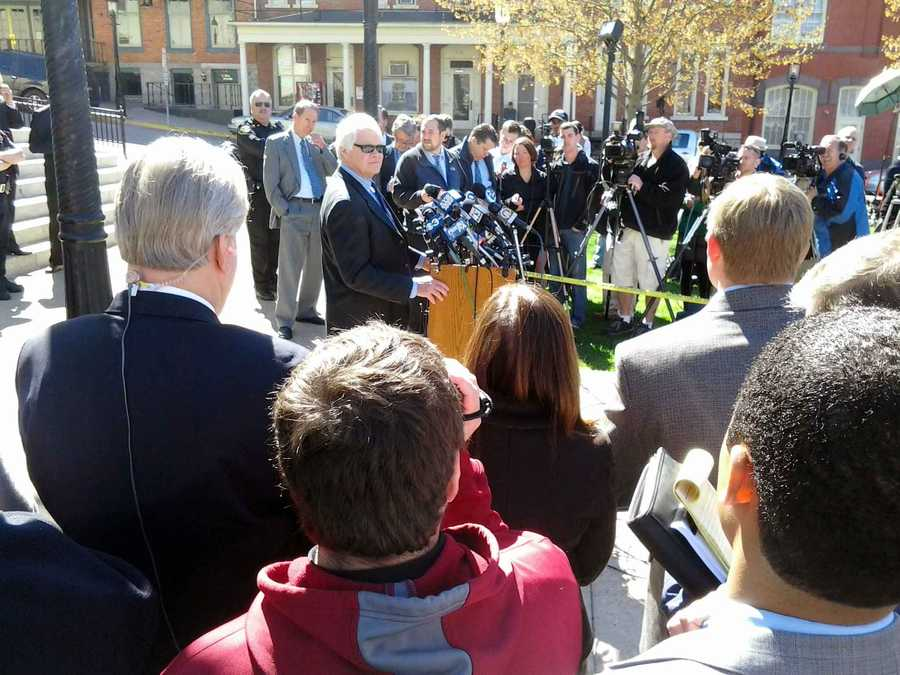A prosecutor talks to reporters in front of the Centre County courthouse.
