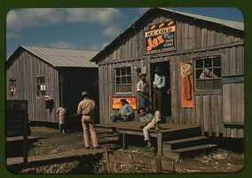 """A cross roads store, bar, """"juke joint,"""" and gas station in the cotton plantation area of Melrose, La. Marion Post Wolcott took this image in June 1940."""