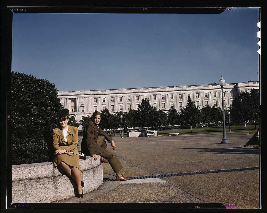 A soldier and a woman in a park, with the Old Russell Senate Office Building behind them in Washington, D.C. The image was taken circa 1943.