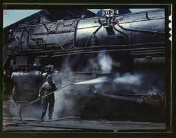 """Mrs. Viola Sievers, one of the wipers at the roundhouse giving a giant """"H"""" class locomotive a bath of live steam in Clinton, Iowa. Mrs. Sievers was the sole support of her mother and had a son-in-law in the Army. Jack Delano captured her portrait in April 1943."""