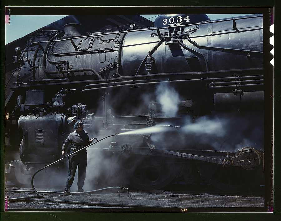 "Mrs. Viola Sievers, one of the wipers at the roundhouse giving a giant ""H"" class locomotive a bath of live steam in Clinton, Iowa. Mrs. Sievers was the sole support of her mother and had a son-in-law in the Army. Jack Delano captured her portrait in April 1943."