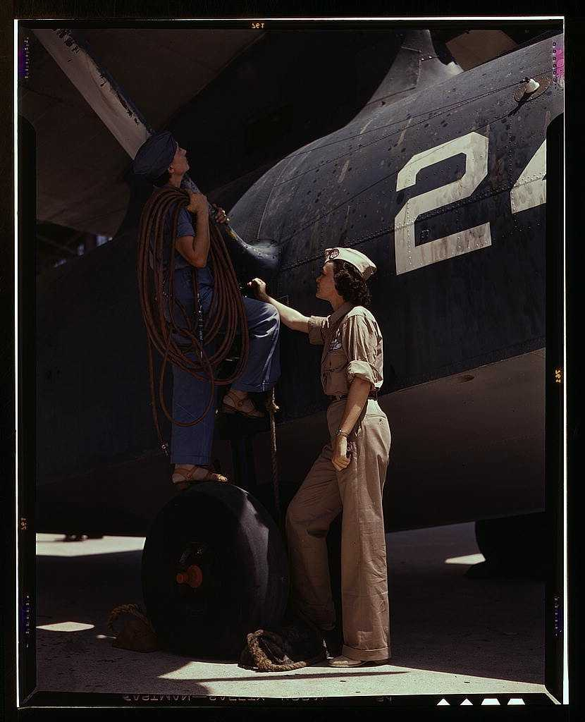 Women contributed their skills to the nation's needs by keeping our country's planes in top-notch fighting condition. The wife of a disabled World War I veteran, Mrs. Cora Ann Bowen (left) worked as a cowler at the Naval Air Base. Howard R. Hollem captured this image in August 1942.