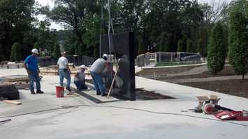 Workers install granite stones Wednesday at the Gold Star Peace Garden at Memorial Park in York.