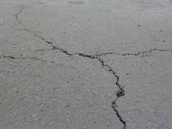 Cracks could be seen in the asphalt near the hole.