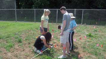 Students at Cedar Cliff High School in Lower Allen Township, Cumberland County, look for artifacts in a mock archaeological dig behind the school's track.
