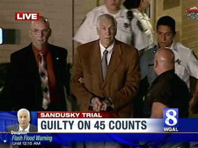 Law enforcement officers lead Jerry Sandusky out of the courthouse in handcuffs.