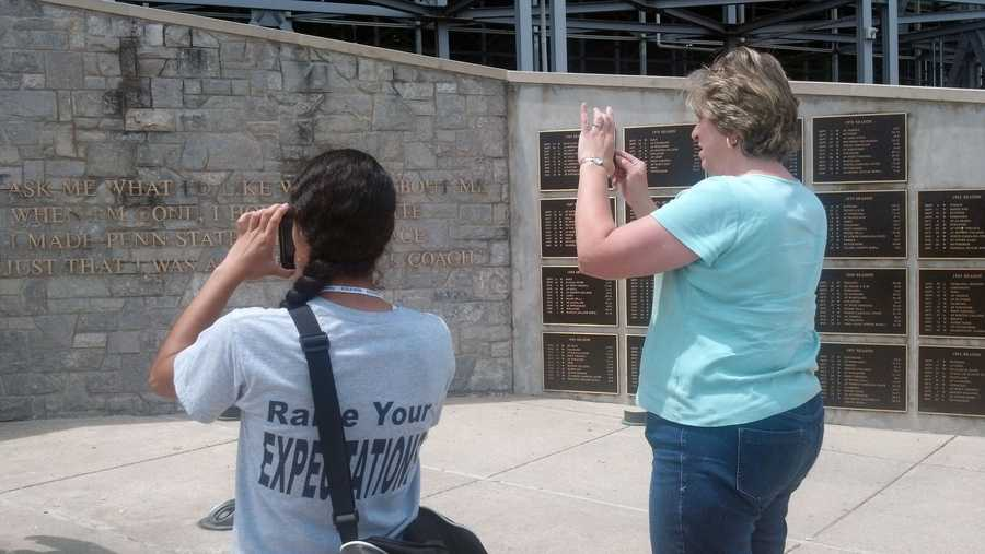 Two people take photos of the statue.