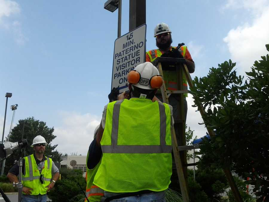Workers take down the sign after removing Joe Paterno statue.