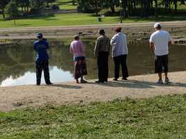 The victim's family gathers at Kiwanis Lake on Monday morning.