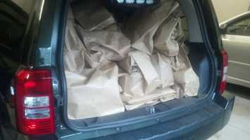 A police vehicle is filled with bags of stolen items.