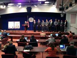 Kelly, flanked by other state officials, addresses reporters.