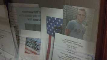 There are also other reminders in the office, like the photos and funeral pamphlets of fallen service members. These are housed in the bookcase behind Platts' desk.