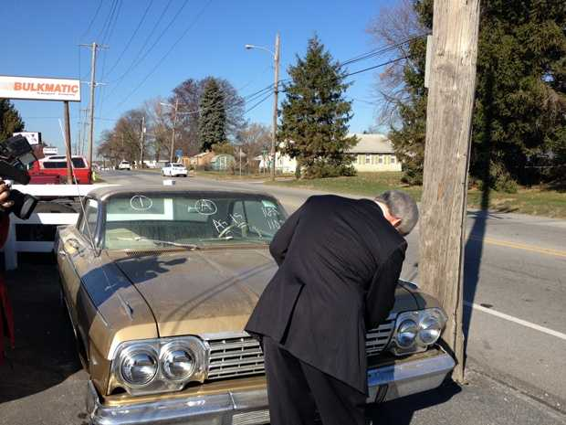 York County District Attorney Tom Kearney takes a look under the hood of a 1962 Chevy Impala, which was part of the auction.
