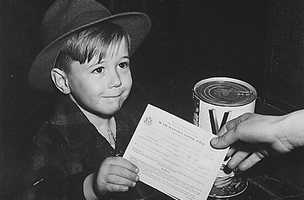 Something known as point rationing was instituted during WW II. During the war a person could not just go into a store and buy as much of certain items as they liked. Some items, such as sugar and meat were rationed. American families were issued war ration books, which could be exchanged for certain goods. This 1943 photo sought to show that the system was so easy that a child could do it.