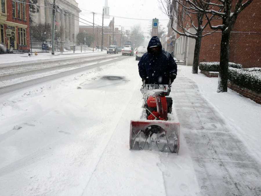 A worker clears snow in front of the Adams County Courthouse.