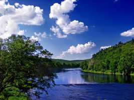 """About 186 miles of the Delaware River are designated as Wild and Scenic. """"The lower Delaware River possesses a great diversity of significant resources. A high density of population and recreational opportunities combine with a wealth of natural, cultural and historic features of national significance. The river valley contains habitats that do not occur elsewhere in the region. For example, there are sheer cliffs that rise 400 feet above the river. Southern facing cliffs are desert-like and home to prickly pear cactus. North-facing cliffs exhibit flora and fauna usually found only in arctic-alpine climates. The river itself provides habitat for American shad, striped bass, and river herring. The river is an important component of the Atlantic Flyway, one of four major waterfowl routes in North America. From an historic viewpoint, the river is one of the most significant corridors in the nation. The corridor contains buildings used during Washington's famous crossing, historic navigation canals, Native American and colonial era archaeological sites and mills. Just as important is the magnificent scenery in the river corridor,"""" states the National Wild and Scenic River System website."""