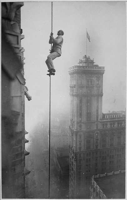 "The time period witnessed a barrage of stunts. This photo was taken around 1918. It shows the ""Human Squirrel"" who did stunts for the benefit of War Relief Funds in New York City. This photo shows him above Times Square."