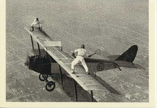 "As time went on, the acts became more and more brazen. This photo shows stunt men Ivan Unger and Gladys Roy ""playing tennis"" on a moving airplane."