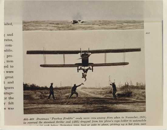 "Pilots would also fly very close to the ground to perform other stunts. Here ""Fearless Freddie"" prepares to grab a hat while hanging upside down from the plane."