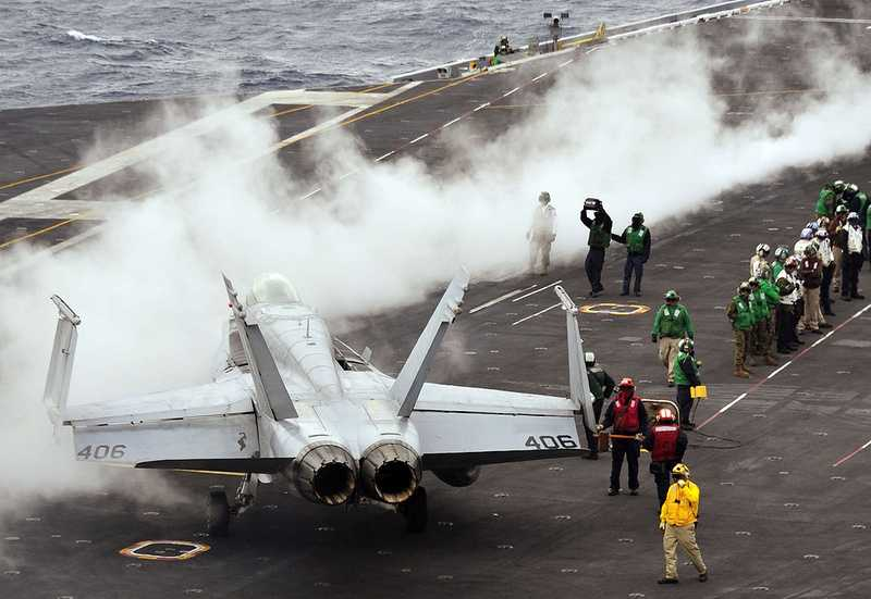 Sailors prepare to launch an F/A-18C Hornet assigned to the Death Rattlers of Marine Fighter Attack Squadron (VMFA) 323 from the flight deck of the aircraft carrier USS Nimitz.
