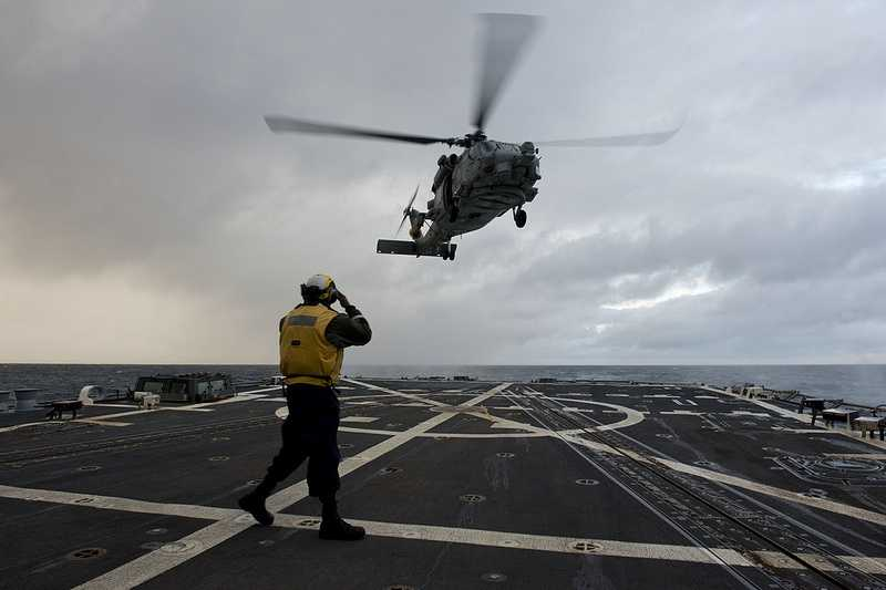In the Philippine Sea, Boatswain's Mate 2nd Class Gerald Battle directs an SH-60 Sea Hawk helicopter assigned to the Warlords of Helicopter Maritime Strike Squadron (HSM) 51 as it lifts off from the flight deck of the Arleigh Burke-class guided-missile destroyer USS McCampbell (DDG 85) following deck landing qualifications.