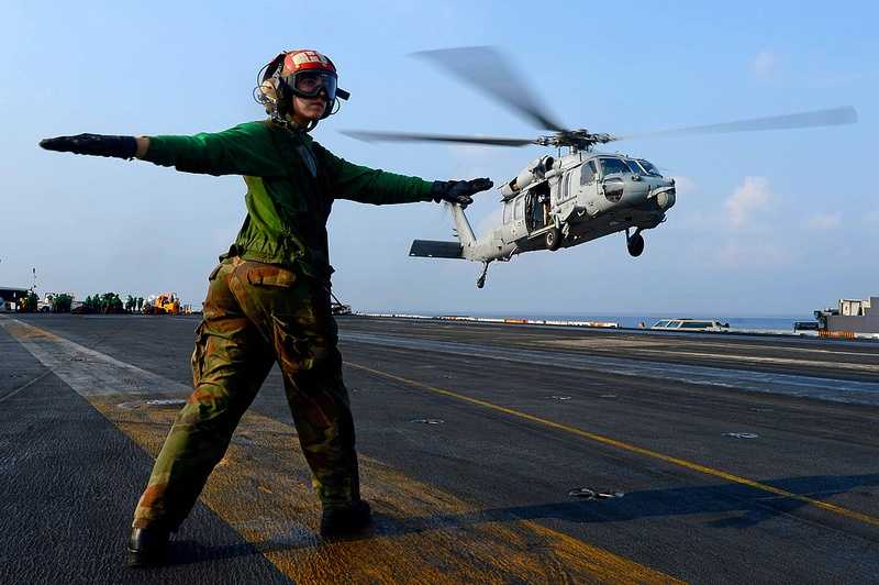 Aviation Structural Mechanic 3rd Class Holly Degroot directs an MH-60S Sea Hawk helicopter from the Eightballers of Helicopter Sea Combat Squadron (HSC) 8 on the flight deck aboard the aircraft carrier USS John C. Stennis (CVN 74).