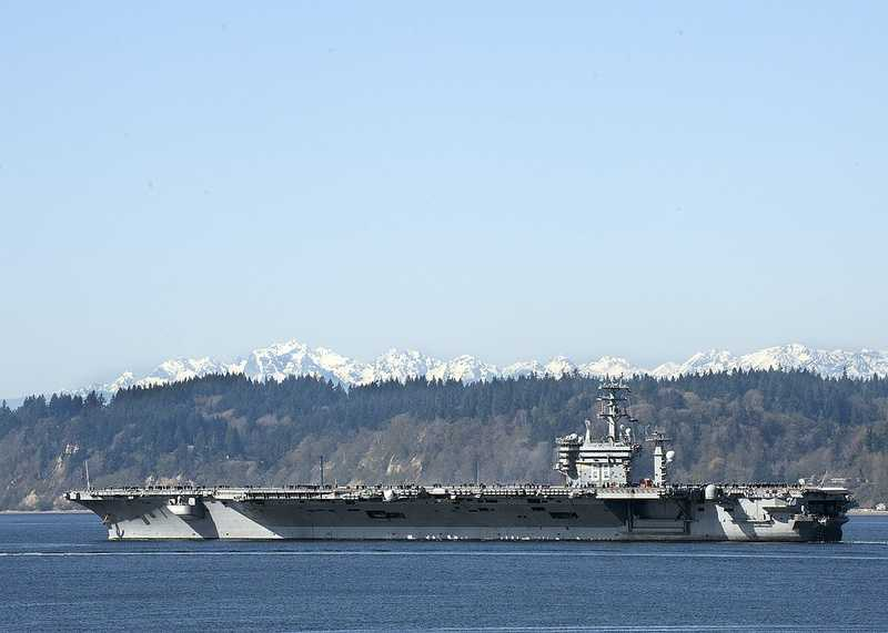 EVERETT, Wash. (March 30, 2013) The aircraft carrier USS Nimitz (CVN 68) passes by the Olympic mountains as it departs for a scheduled deployment from its homeport, Naval Station Everett.